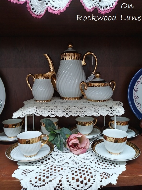 Gold and white tea cup set displayed on white doilies
