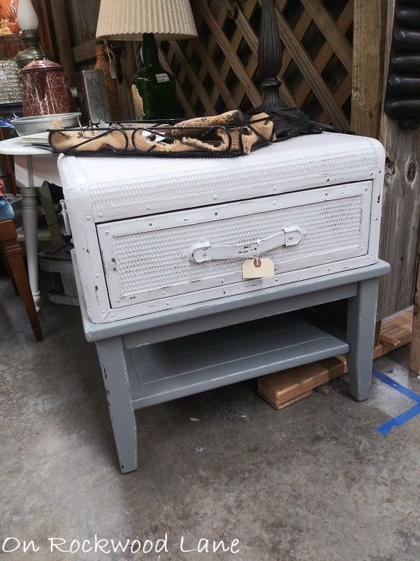 gray side table that has an old luggage glued on top that opens for storage