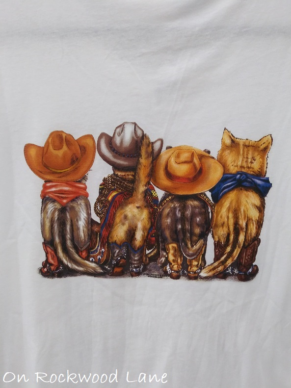 Backside of white t-shirt with cats dressed like cowboys