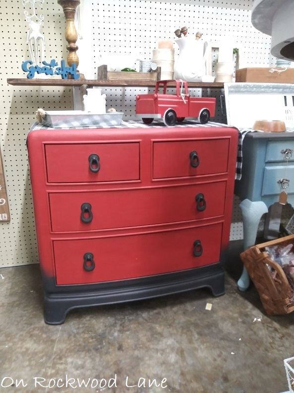 upcycled red and black dresser with plaid table runner and red truck on top
