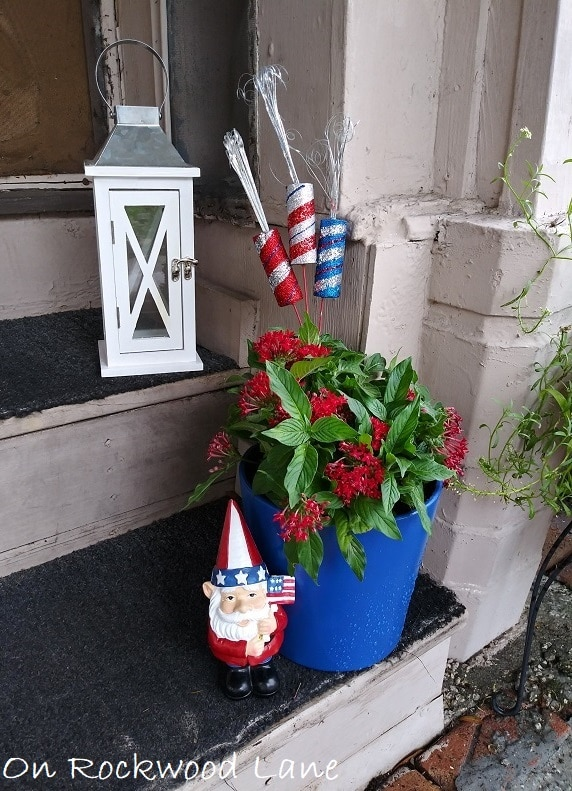 Small porch 4th of July decor with white lantern, blue planter with red flowers, styrofoam firecracker picks and patriotic gnome, On Rockwood Lane