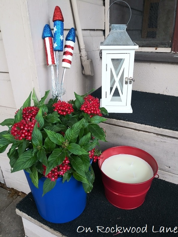 Small porch 4th of July decor with white lantern, blue planter with red flowers, and citronella candle, On Rockwood Lane